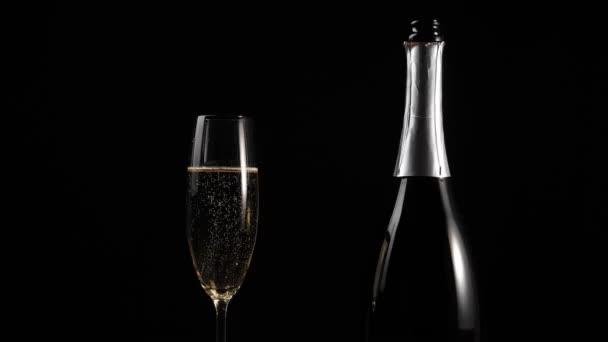 Sladké šampaňské. Sklenice se zlatým šampaňským a láhev se šampaňským na dřevěném stole proti černému pozadí. Flétny se šumivým vínem. Novoroční párty. Oslava. 4k