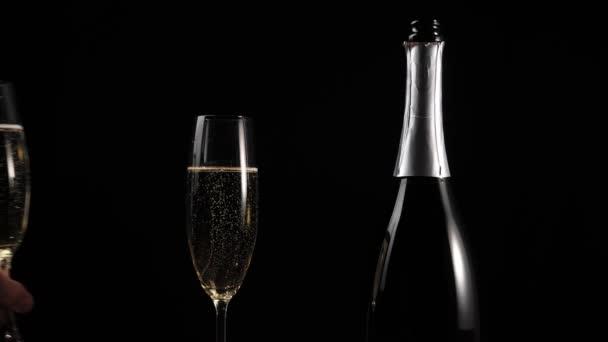 Sladké šampaňské. Ruka položí sklenici se zlatým šampaňským na dřevěný stůl vedle jiného skla a láhev na černém pozadí. Flétny se šumivým vínem. Novoroční párty. Oslava. 4k