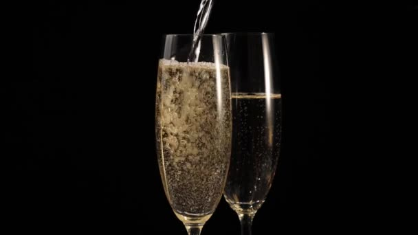 Sladké šampaňské. Dvě sklenice se šampaňským na černém pozadí. Flétny se šumivým vínem. Ruka nalévá do sklenic zlaté šampaňské. Novoroční párty. Oslava. Střední střela. 4k