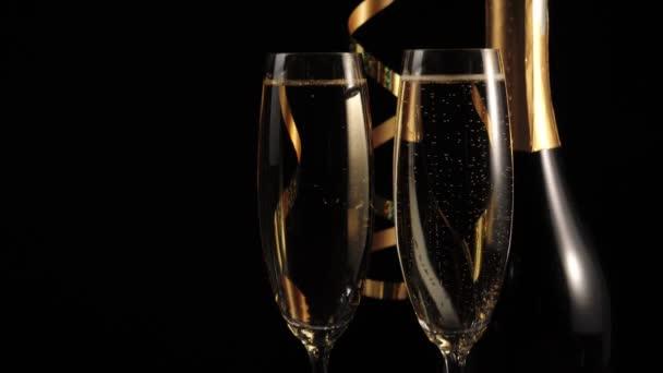 Sladké šampaňské. Dvě sklenice se zlatým šampaňským a láhev se šampaňským a zlatou stuhou na dřevěném stole na černém pozadí. Flétny se šumivým vínem. Nový rok. Oslava. 4k