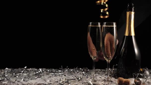 Édes pezsgő. Két pohár pezsgővel és üveg fekete háttérrel. Furulyák pezsgővel. A kéz vesz egy poharat arany pezsgővel. Újévi buli. Ünneplés. 4k