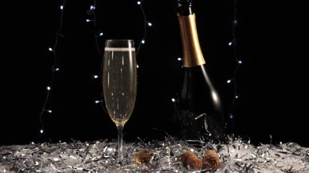 Sladké šampaňské. Ruka vezme sklenici se zlatým šumivým vínem ze stolu s bílým sněhem a konfety proti světlu v pozadí. Vánoční a novoroční dekorace. 4k