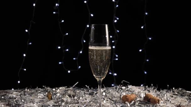 Édes pezsgő. Kézzel vesz egy pohár arany pezsgő asztalról fehér hó és konfetti ellen fények a háttérben. Karácsonyi és újévi dekorációk. 4k