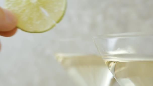 Luxus-Martini. Hand legt eine Scheibe Limette auf den Rand eines Martini-Glases auf den Tisch, der mit Oliven, Sticks, Limette und Minze vor hellem Hintergrund dekoriert ist. Wermut plätschernde Wellen, Cocktailparty. 4k