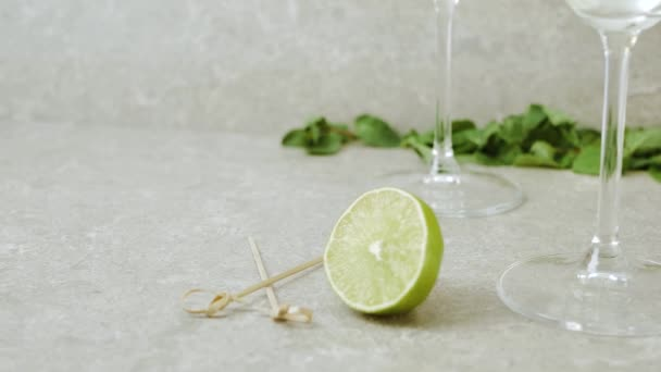 Luxus-Martini. Hand legt eine Schüssel mit Oliven auf den Tisch, dekoriert mit Cocktailstangen, Limette, Minze und Gläsern mit Martini vor hellem Hintergrund. Wermut plätschernde Wellen. Mittelschuss. 4k