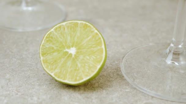 Luxus-Martini. Tisch mit Oliven, Cocktailstangen, Limette und Minze vor hellem Hintergrund. Kamera bewegt sich aus dem Glas mit Martini auf der grünen Limette. Mittelschuss. 4k