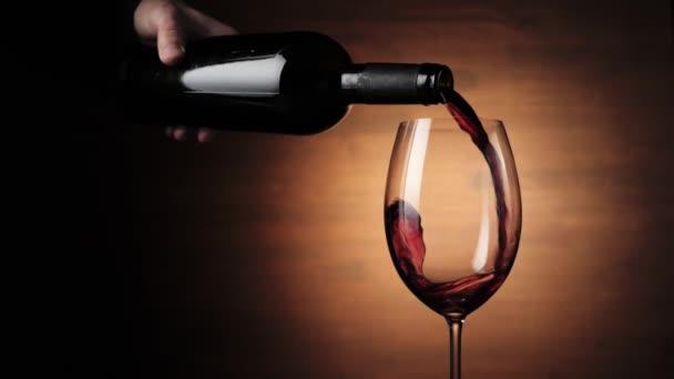 Luxus vörösbor. Kézzel öntött finom bort a palackból borospohárban, barna háttér mellett. Ízletes vörös szőlőből készült rózsabor, amely a palackból a serlegbe ömlik. Lassú mozgás.