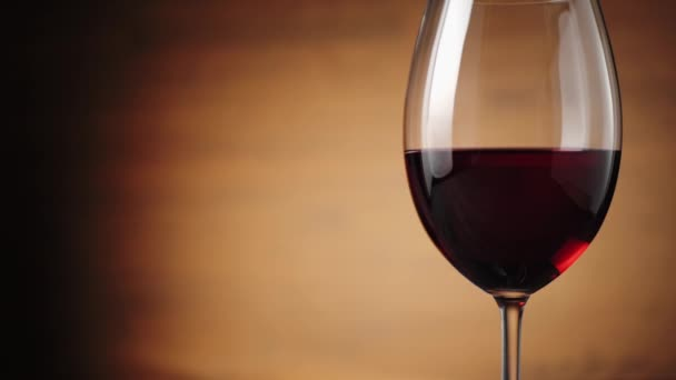 Luxury red wine. Delicious wine, made from delicious red grapes in wine glass on the table against brown background. Camera moves up. Slow motion