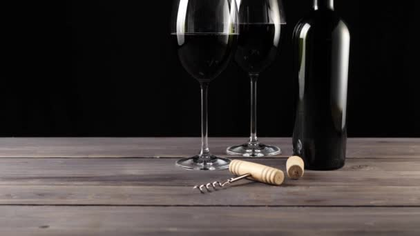 Luxury red wine. Two wine glasses, corkscrew, cork and bottle of red wine, made from delicious red grapes on the table against black background. Slow motion. Middle shot. Camera moves up. 4K