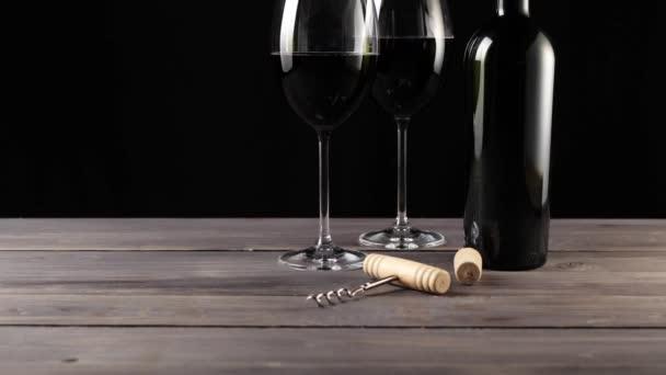 Luxus-Rotwein. zwei Weingläser, Korkenzieher, Korken und eine Flasche Rotwein, hergestellt aus köstlichen roten Trauben auf dem Tisch vor schwarzem Hintergrund. Zeitlupe. Mittelschuss. Kamera rückt an. 4k