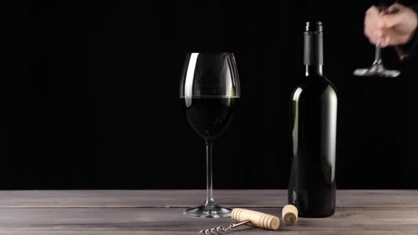 Luxury red wine. Two wine glasses, corkscrew, cork and bottle of red wine, made from delicious red grapes on the table against black background. Hand puts a glass. Slow motion. Middle shot. 4K