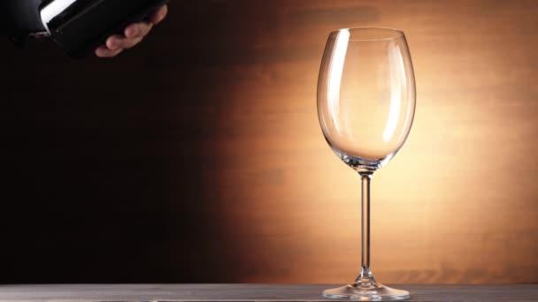 Luxus-Rotwein. Hand gießt köstlichen Wein aus der Flasche in Weinglas vor braunem Hintergrund. Rosenwein aus köstlichen roten Trauben, die aus der Flasche in den Becher fließen. Zeitlupe. 4k