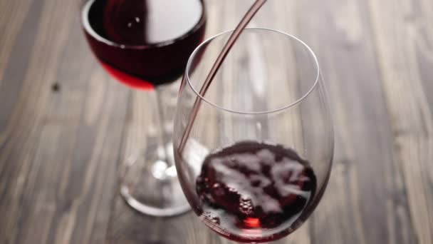 Luxus vörösbor. Kézzel öntött finom bort a gejzír borospohárban asztalhoz. Ízletes vörös szőlőből készült rózsabor, amely a palackból a serlegbe ömlik. Első látásra. 4k
