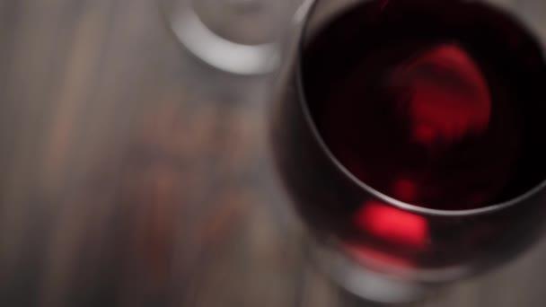 Luxus-Rotwein. zwei Weingläser mit Wein aus köstlichen roten Trauben auf dem Tisch. Kamera geht nach unten. Zeitlupe. Ansicht von oben. 4k