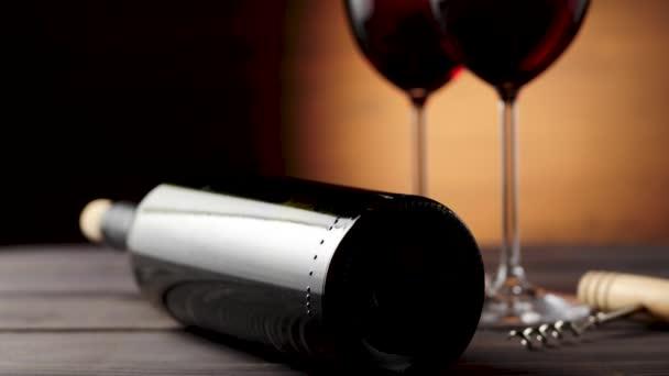 Luxusní červené víno. Dvě sklenice vína s vínem, z lahodných červených hroznů, vývrtka a láhev s vínem na stole. Kamera jede nahoru. Zpomal. Střední střela. 4k