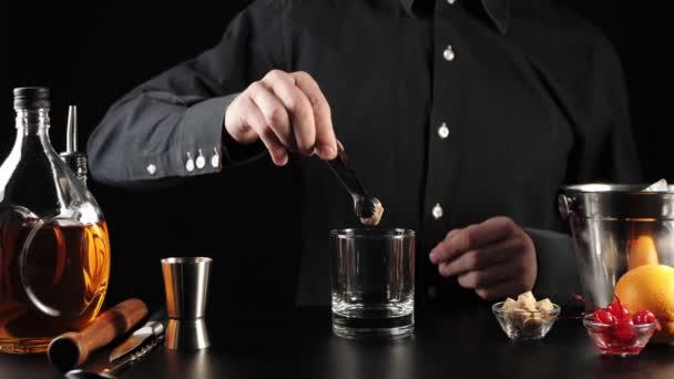 Starý módní koktejl. Barman si vezme kostku cukru s pinzetou a dá ji do skla. Pak si nalije pár kapek angostury. Oficiální koktejl Iba. Čas se napít. Široký záběr