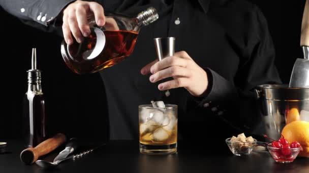 Starý módní koktejl. Barman si dá džigger, nalije do něj bourbon z kulaté láhve a nalije do něj druhou porci bourbonu. Oficiální koktejl Iba. Široký záběr