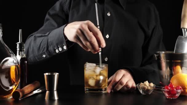 Starý módní koktejl. Barman míchá cukr, angosturu, kostky ledu a bourbon ve skle s barmanskou lžičkou. Sklenice se ochladí na čerstvost. Oficiální koktejl Iba. Široký záběr