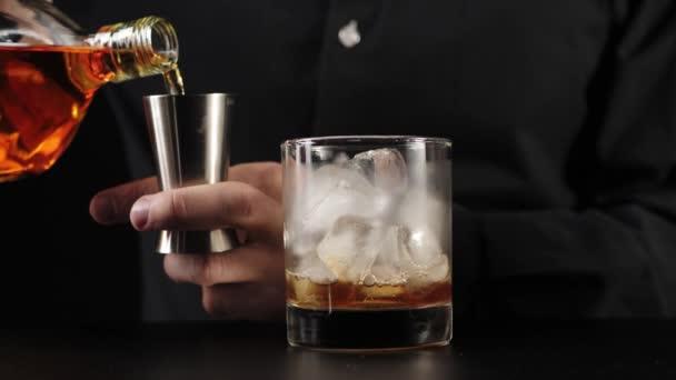 Starý módní koktejl. Barman si vezme jigger, nalije do něj bourbon z kulaté láhve a nalije obsah do sklenice. Oficiální koktejl Iba. Střední střela