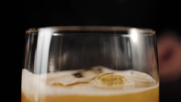 Whiskey Sour cocktail. Bartender takes a slice of orange and puts it in a rocks glass with Whiskey Sour cocktail. Decorates the cocktail with delicious red cherry. IBA official. Slow motion. Close up