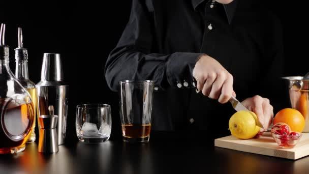 Whisky Kyselý koktejl. Barman vezme nůž a rozřízne žlutý šťavnatý citron na dřevěnou desku. Půl citronu kapky na černém stole na černém pozadí. Oficiální koktejl Iba. Široký záběr