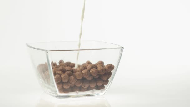 Čerstvé zdravé jídlo. Mléko nalévající se do průhledné misky s čokoládovými cereáliemi na bílém pozadí. Koncept zdravé snídaně, čisté stravování, diety, vegetariánské, veganské jídlo. Boční pohled