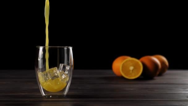 Große Aufnahme von frischem Orangensaft, der in doppelwandigem Glas mit Eiswürfeln auf einem Holztisch mit köstlichen Orangen im weichen Fokus im Hintergrund vor schwarzem Hintergrund ausgeschenkt wird.