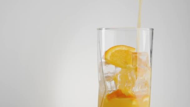 Frischer Orangensaft wird in ein transparentes Glas gefüllt, das mit Eiswürfeln und Orangenscheiben vor hellem Hintergrund dekoriert ist. Das Konzept einer gesunden und sauberen Ernährung, Ernährung, vegetarische Kost. Mittelschuss