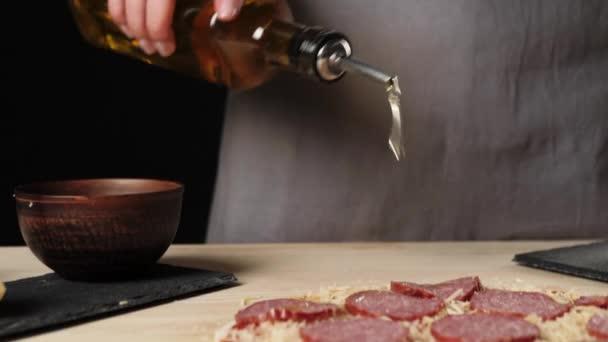 Profesionální kuchař posype pizzu olivovým olejem, aby zvýraznil chuť na stole zdobené ingrediencemi pizzy. Koncept těsta hnětení a vaření lahodné pizzy. Zavřít. 4K