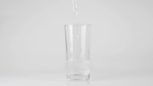 Pure fresh water is poured into a transparent glass on a white background. Concept of stay at home and eat healthy food with natural water. Detoxication. Middle shot. Slow motion