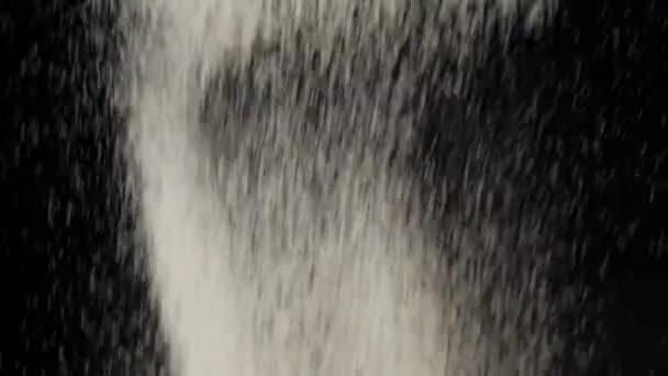 Mehl fliegt und fällt vor schwarzem Hintergrund herunter. Weißes Pulver und herabfallende weiße Teilchen fliegen auf den Hintergrund. Konzept des Teigknetens und Kochens leckerer Pizza. Zeitlupe