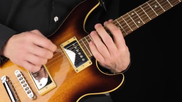 Guitarist plays a light brown six-string electric guitar with a pick against black background. Concept of stay home and make some music. Free time for sound art. Middle shot. 4K