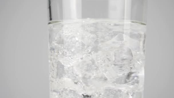 Ice cubes spin and float in a glass with pure fresh water with bubbles against white background. Concept of stay at home and eat healthy food with natural water. Close up. Slow motion