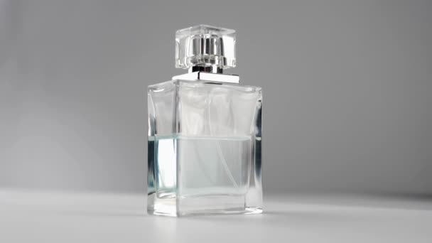 Flat surfaced bottle with cyan perfumes or essential oils slowly rotates on the white table against grey background. Concept of aroma and smell. Close up. Slow motion