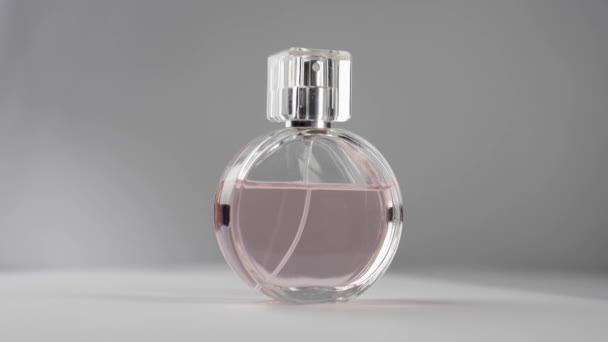 Oval surfaced bottle with pink perfumes or essential oils slowly rotates on the white table against grey background. Concept of aroma and smell. Close up. Slow motion