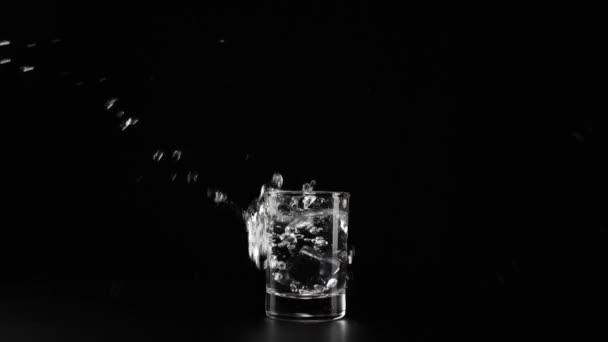 Eiswürfel fällt mit Spritzern und Blasen in Schnapsgläser mit Wodka, Tequila oder Sake auf schwarzem Tisch vor schwarzem Hintergrund. Vorbereitung auf den Alkoholkonsum. Mittelschuss. Zeitlupe