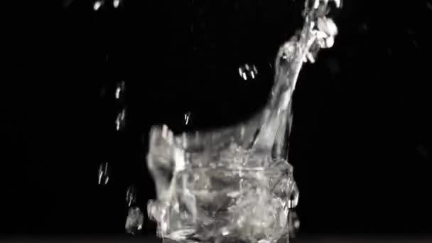 Eiswürfel fällt mit Spritzern und Blasen in Schnapsgläser mit Wodka, Tequila oder Sake auf schwarzem Tisch vor schwarzem Hintergrund. Vorbereitung auf den Alkoholkonsum. Extrem hautnah. Zeitlupe