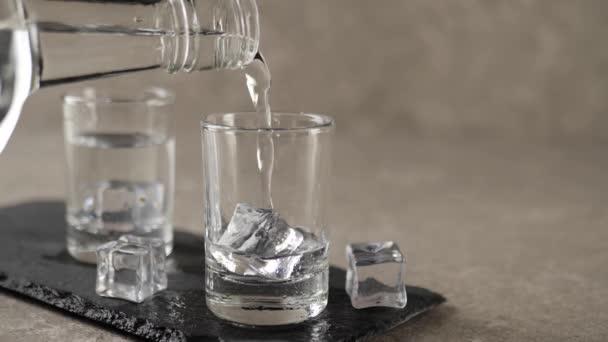 Hand gießt Wodka, Tequila oder Sake aus einer flachen Flasche in leeres Schnapsglas auf schwarzem Brett, das mit Eiswürfeln und Vollkugelglas vor Marmorhintergrund dekoriert ist. Zeit, Alkohol zu trinken. Nahaufnahme