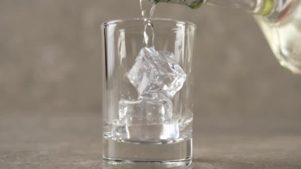 Ruka nalije vodku, tequilu nebo saké z ploché láhve do sklenice s ledovými kostkami na mramorovém stole na mramorovém pozadí. Čas na alkohol. Zavřít. Zpomalený pohyb