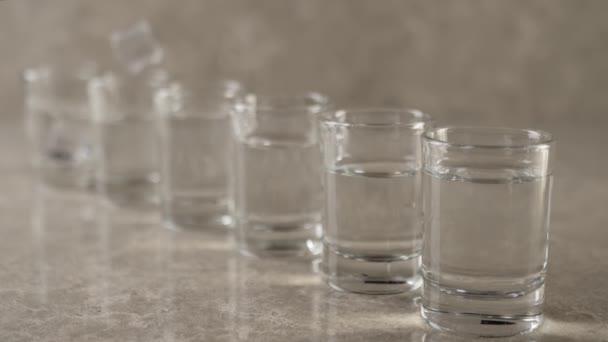 Ledové kostky padají s cákancemi a bublinkami do šesti sklenic s vodkou, tequilou nebo saké na mramorovém stole na mramorovém pozadí. Střední střela. Zpomalený pohyb