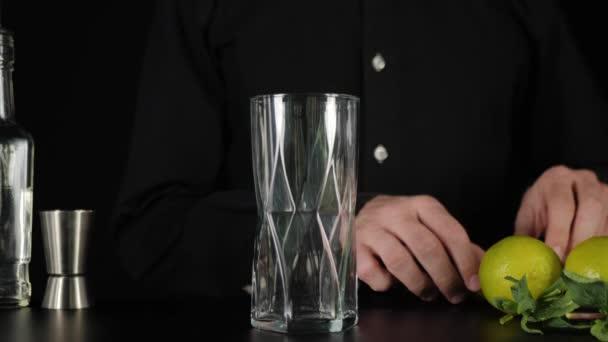 Friss mojito. A csapos feldarabol egy zöld lime-ot egy acél késsel, és fekete háttér elé teszi a magas üvegbe. A mojito elkészítésének koncepciója. IBA koktél. Közelről. 4K