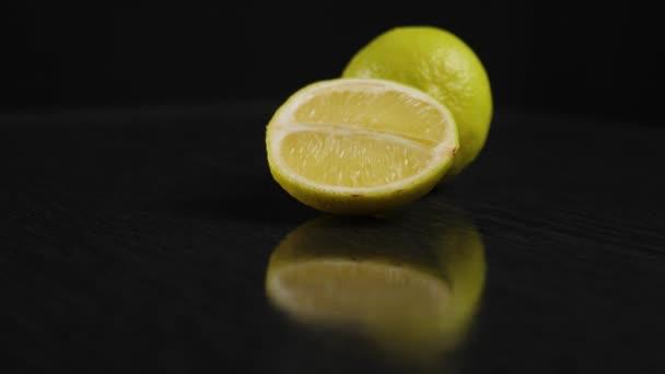 In der Mitte drehen sich auf einem schwarzen Tisch vor schwarzem Hintergrund vereinzelt frische grüne Limetten um die eigene Achse. Konzept der Frische und Mojito-Zubereitung. Aus nächster Nähe. 4K