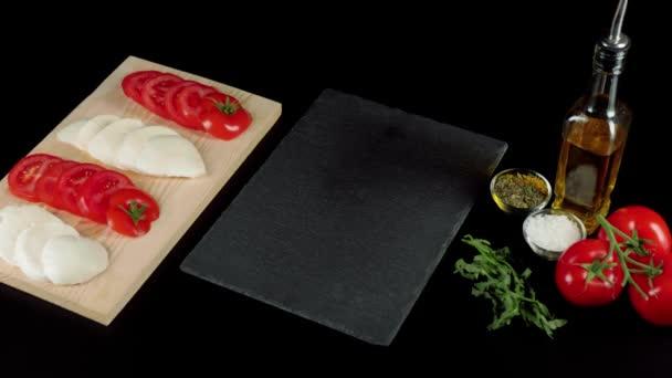 Moderní caprese salát. Čerstvé šťavnaté červené rajčata na větvi, mozzarella sýr, listy rukoly, olivový olej a mořská sůl na černém pozadí. Kamera se pohybuje vpřed. Dolly zoom. Horní pohled