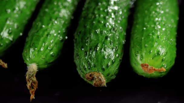 A kamera a friss zöld lédús uborka fölé kerül egy fekete táblán, a fa asztalon. A friss nyári saláta elkészítésének koncepciója. Első látásra. Lövés. 4K