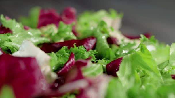 Kamera se pohybuje nad svěžím šťavnatým barevným zeleným a kaštanovým salátem na dřevěném stole. Koncept výroby čerstvého letního salátu ze salátu, cherry rajčat, okurek a cibule. Horní pohled. Za ním. 4K