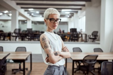 In her own style. Portrait of young and attractive blonde tattooed businesswoman in eyeglasses keeping arms crossed and looking at camera while standing in modern working space