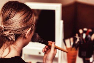 Back view teenage girl applies makeup with brush