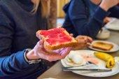 Fényképek Kézzel tart egy darab kenyeret, piros lekvárral