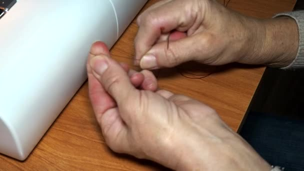 adult female seamstress ties a knot on a thread. Hands close up. The woman makes an even line. Making clothes and sewing bed linen at home or in a garment factory