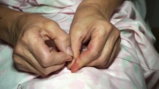 adult female seamstress inserts a thread into a needle. Hands close up. grandma makes a smooth hand stitch. Making clothes and sewing colored bed linen at home or in a garment factory